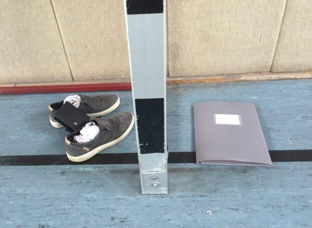 Schuhe und Mappe, die symbolisch links und rechts eines Pfostens liegen.
